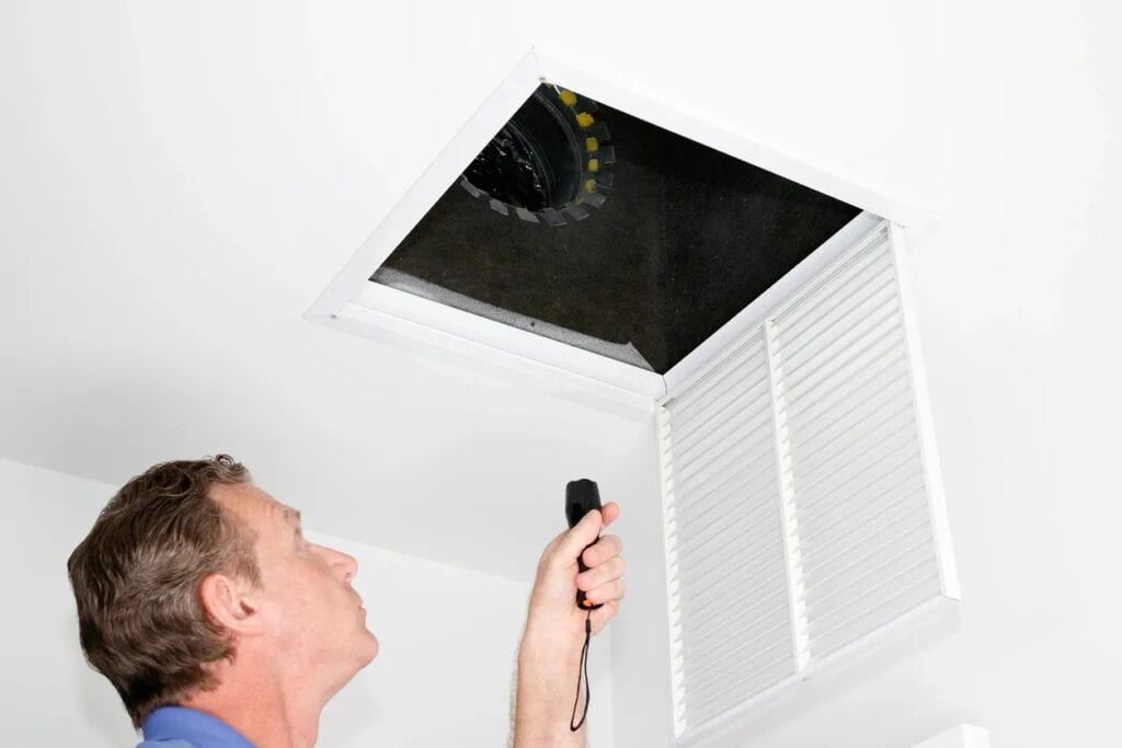 man inspecting HVAC vent